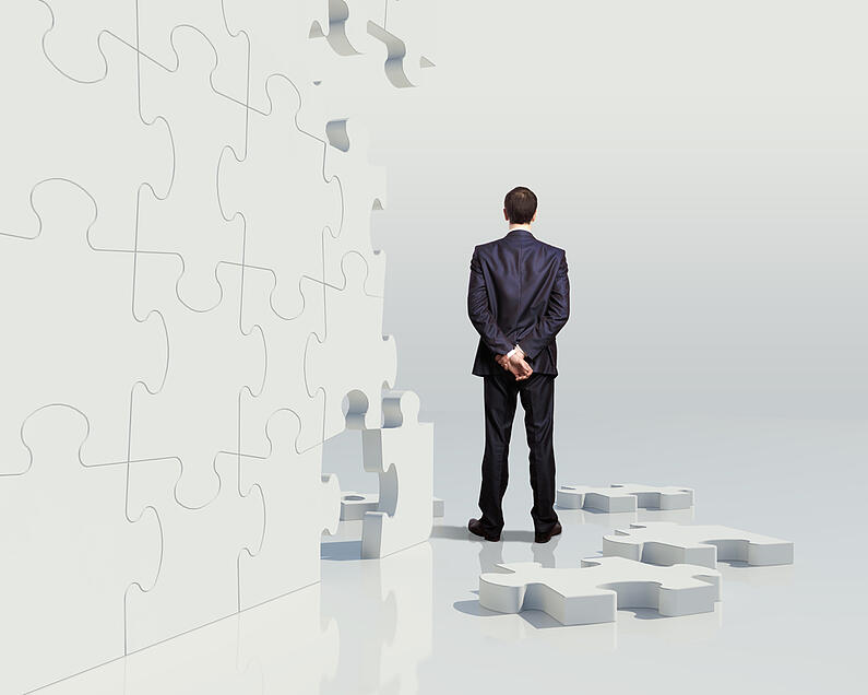 Businessman with a puzzle pieces on the background, as a concept of elements of an innovation team