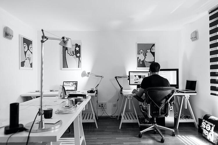 Man sitting at his desk with 2 monitors and a laptop, in a beautiful office, with retro paintings on the wall, as a concept of rapid prototyping