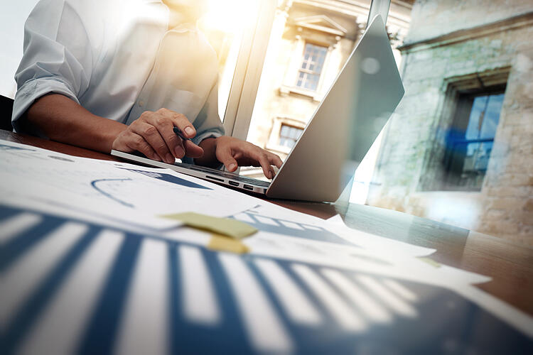 business documents on office table with smart phone and digital tablet and graph financial diagram and man working in the background, as a concept of what is rapid prototyping