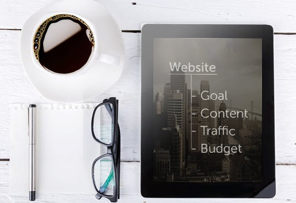 Close-up of a tablet, a cup of dark coffee, black framed eyeglasses and a silver pen on a wooden desk