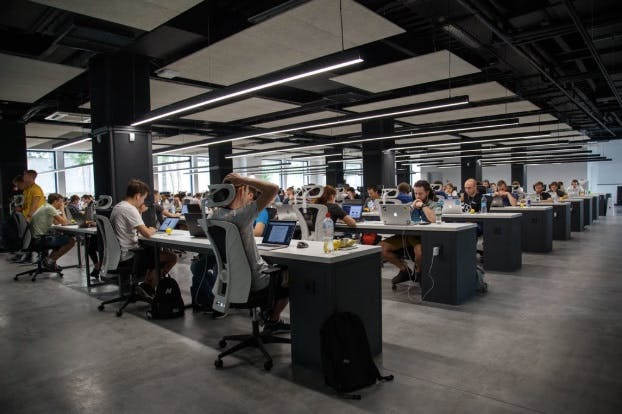 Developers working in a huge office, with ergonomic chairs and MacBooks on their desks
