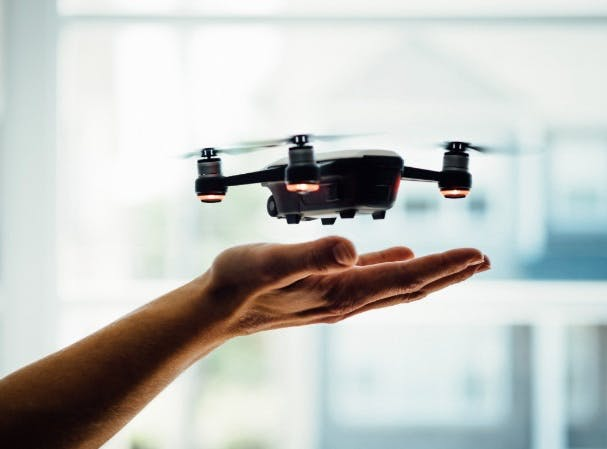 Close-up of a drone flying over a man's open palm