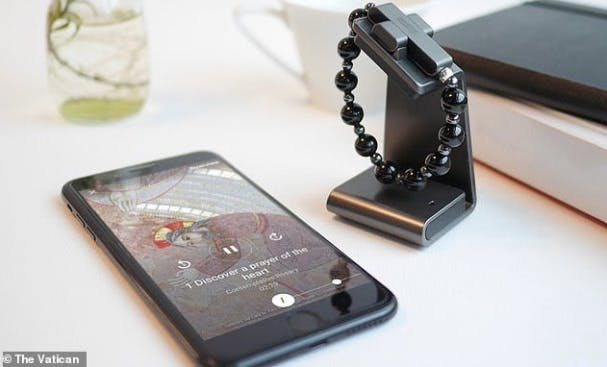 Close-up of eRosary black beads and an iPhone on a white desk