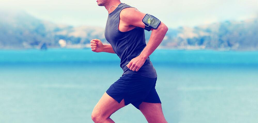 Fit man running outdoors, with an iPhone displaying SportMe app,  inside an armband, as a concept of running training plan