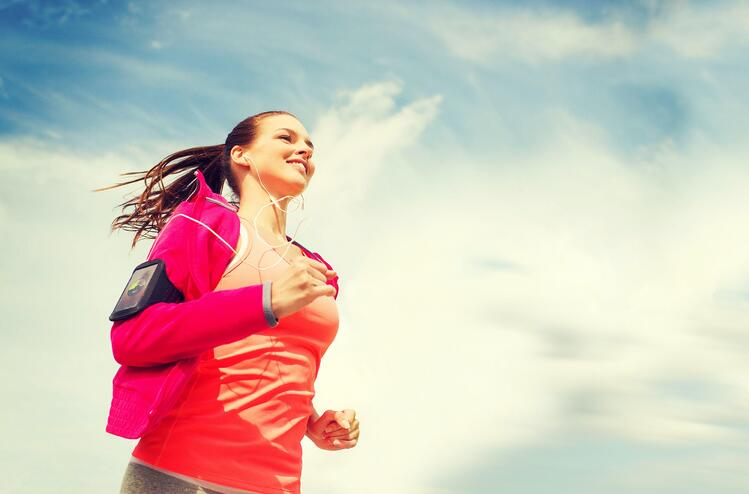 woman with an iPhone in an armband, running and smiling, with a blue sky as backgound