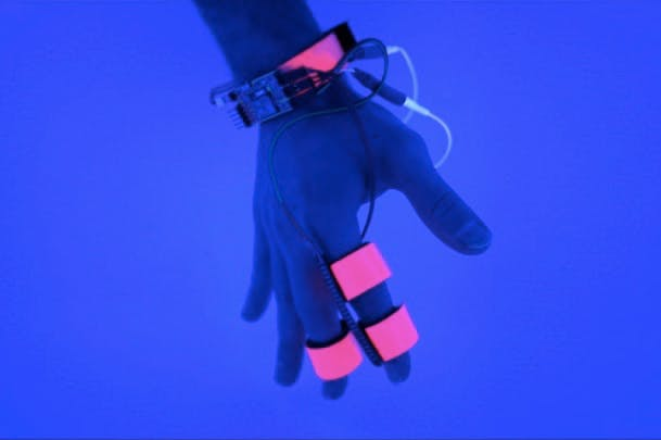 hand connected to sensors, on blue