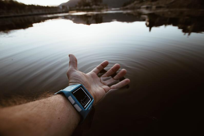 man's hand with smartwatch emerging into water, as a concept of federated learning definition