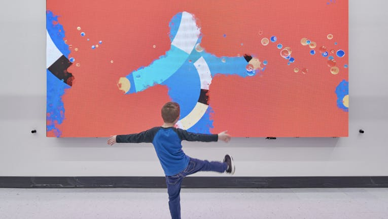 kid playing in front of a wall