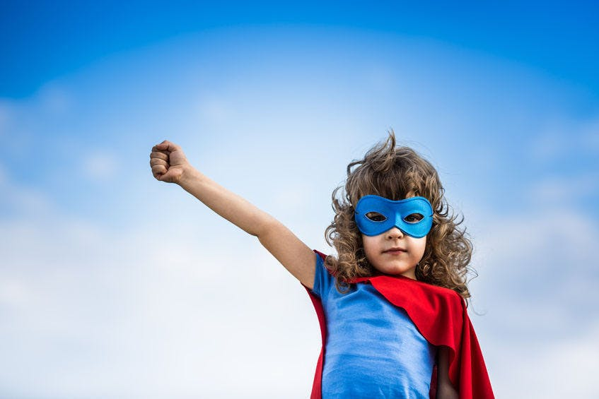 A little brown haired girl dressed in Super Man costume, with her right hand raised and a blue sky as background