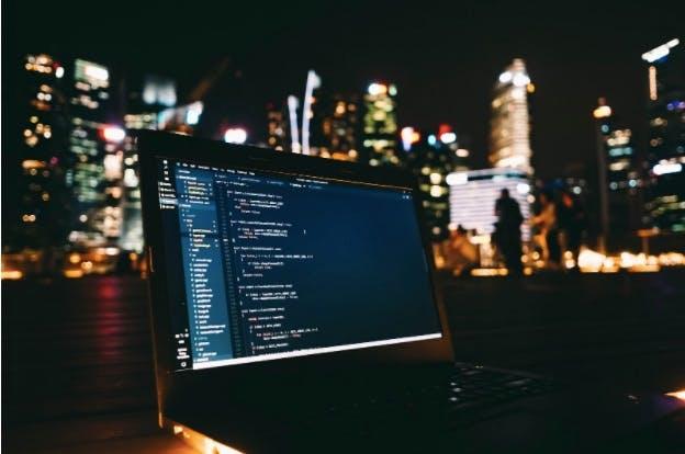 Laptop coding Firebase vs AWS in city night