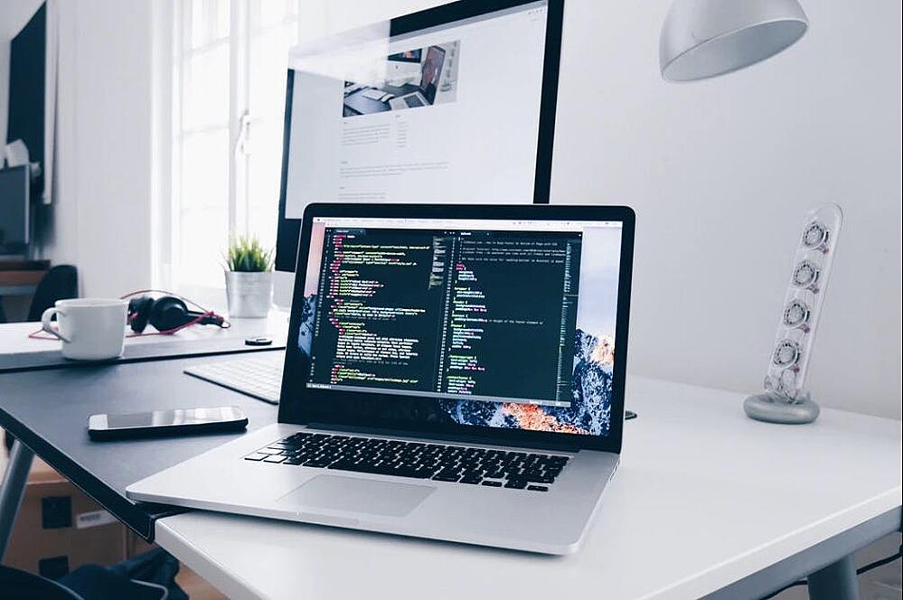 minimalist office with Apple devices, as a concept of custom software development and of react js