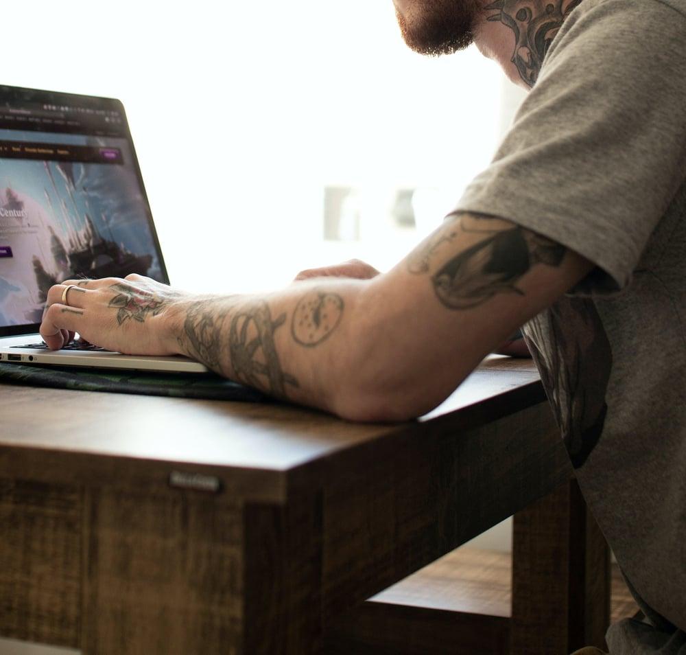 man at his computer, at a wooden desk