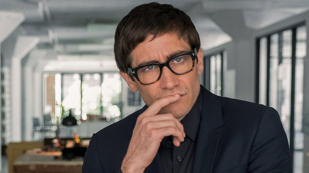 close-up image of a man with glasses as a pose of thinking