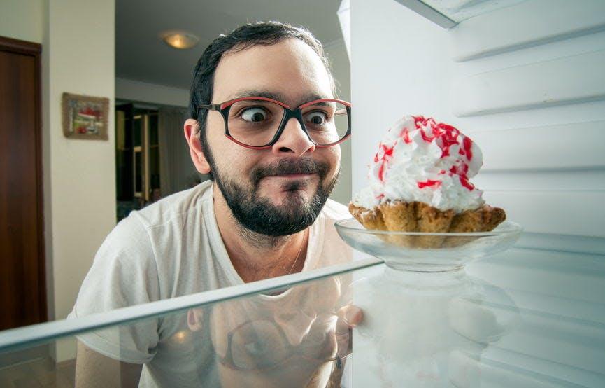 man with eyeglasses staring at a cake