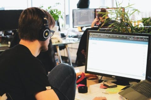 A man in headphones working at a computer, as a concept of enterprise web development