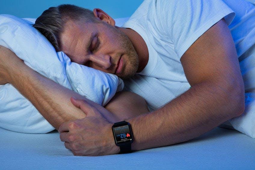 man sleeping with a smart watch. sleep monitor