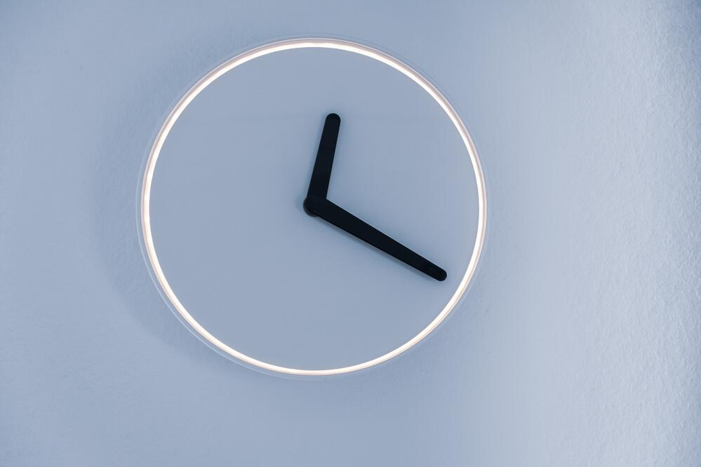 minimalist image of a neon clock, as a concept of fixed vs hourly software development cost