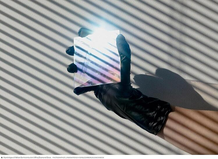 Close-up of a hand with a black glove, holding a mirror reflecting the light