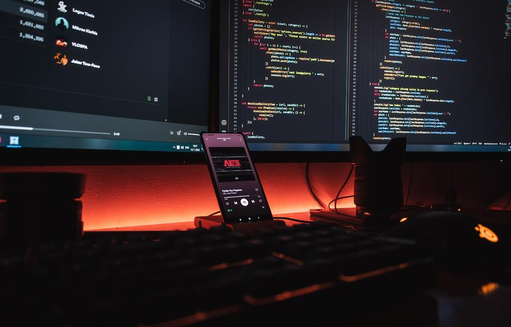 Double computer screens with a smartphone on a desk, as a concept of firebase vs heroku