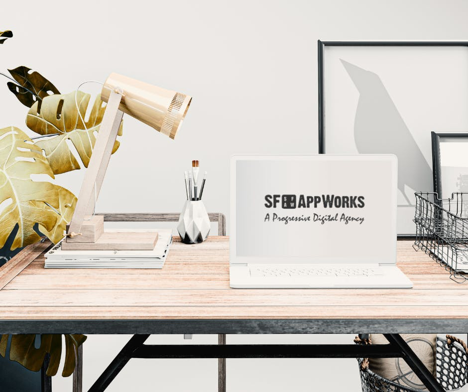 office decor, white laptop on a wooden desk, as a concept of SF AppWorks, a top mobile development company