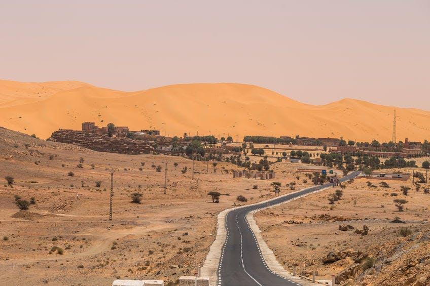 a road through the desert and a town far away