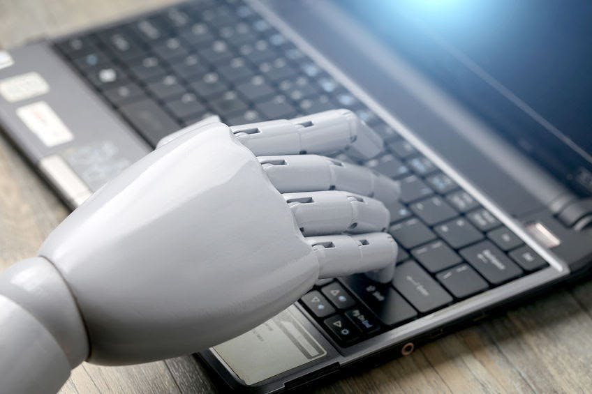 Close-up of a robotic hand typing