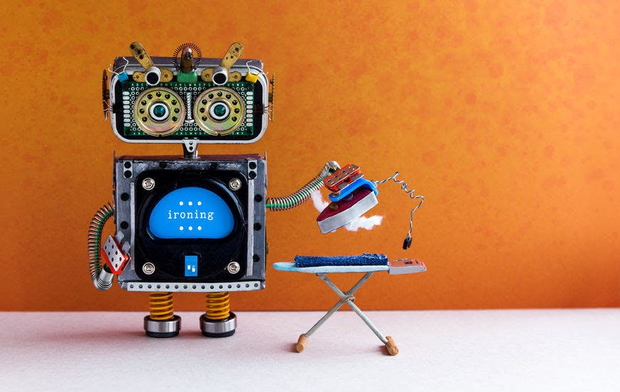 robotic housework assistant ironing blue jeans with iron on the board. orange wall gray floor room interior. creative design toys housework concept. copy space.