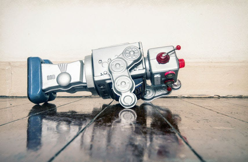 Over worked retro silver robot facedown on old wooden floor with reflection
