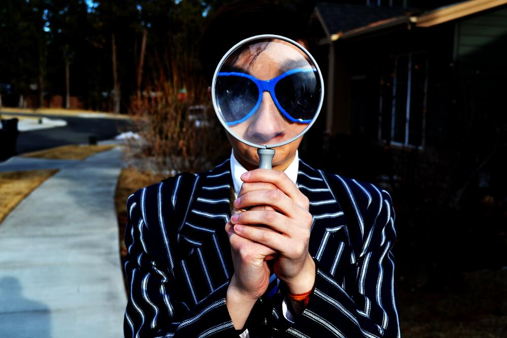 person with sunglasses looking through a magnifier glass, as a concept of innovation as a daily practice