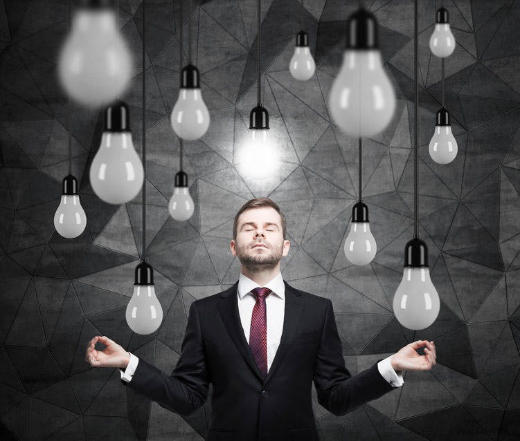 Man dressed in suit, surrounded by light bulbs, of which one is lit
