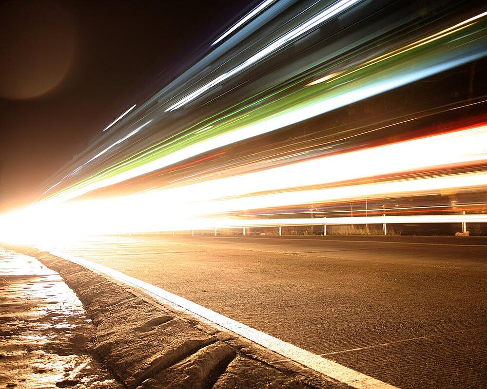 speed concept, colorful lights above a concrete road.