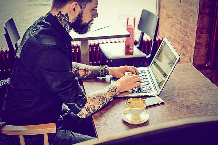 Close-up of tattooed man typing at his desk, with a cup of coffee by his side