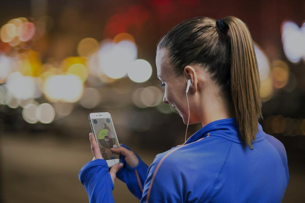 woman preparing to run looking at SportMe running app on an iPhone screen