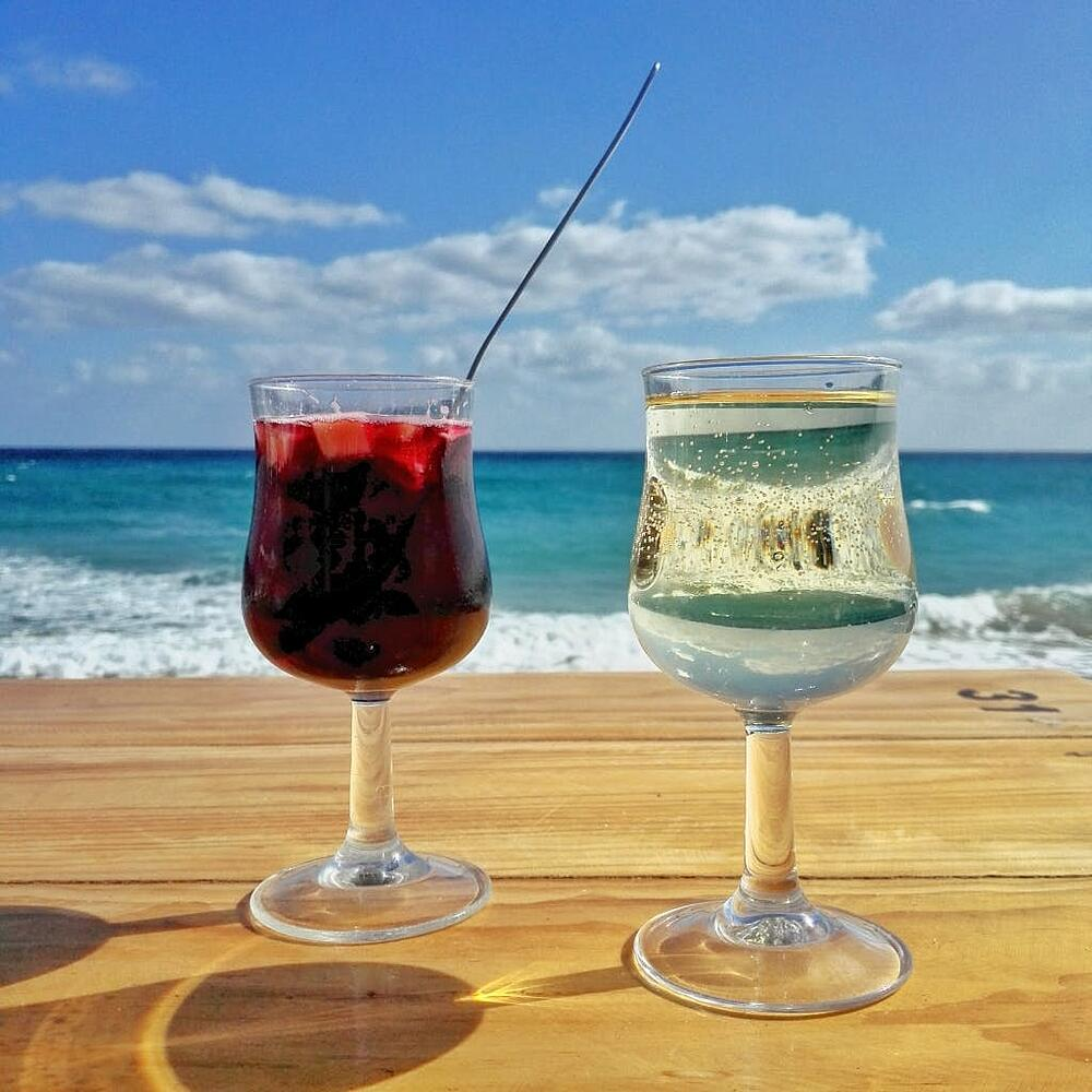cocktail glasses on a wooden table, in front of the ocean