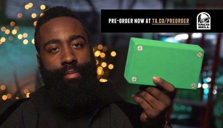 Close-up of a man holding a green box as a package from Taco Bell