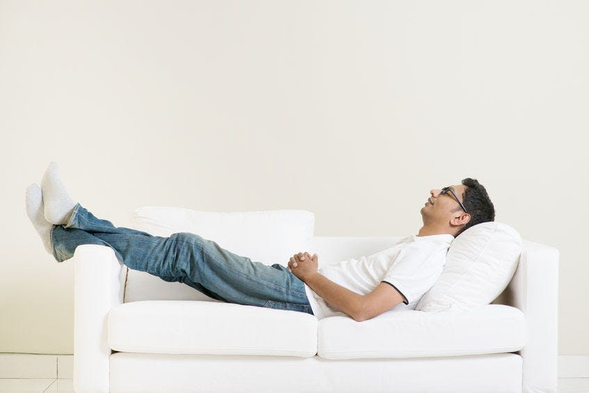 Man with eyeglasses, dressed in worn blue jeans and a white T shirt, lying comfortably on a white Scandinavian couch