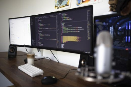 A computer set up with a large monitor showing code, as a concept of enterprise web development