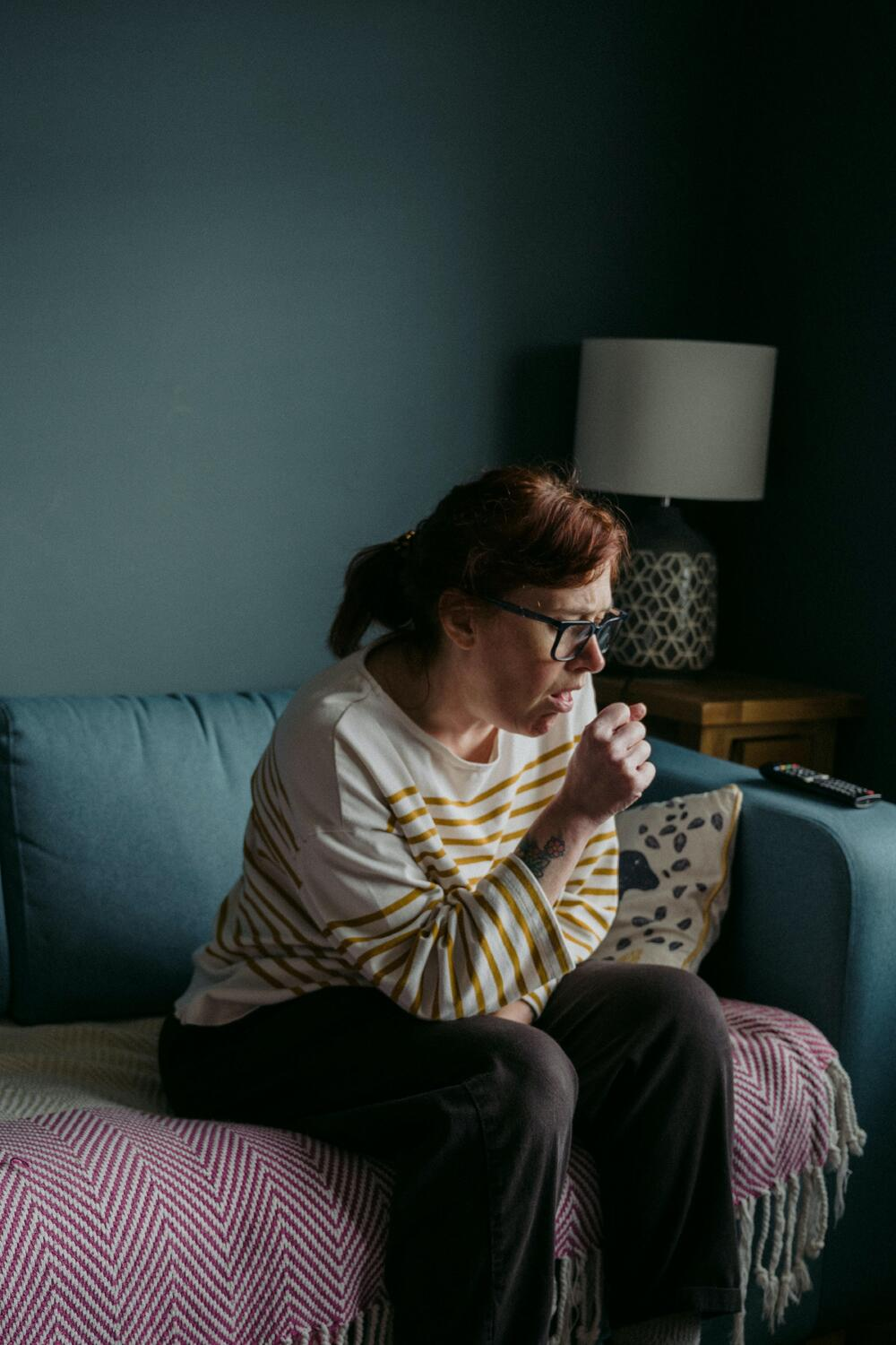 woman sitting on a couch coughing