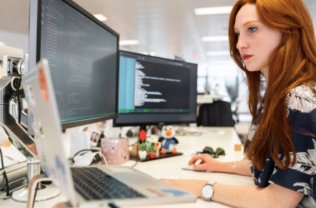 red-haired woman working in front of 3 computer monitors, as a concept of website development, types of application development