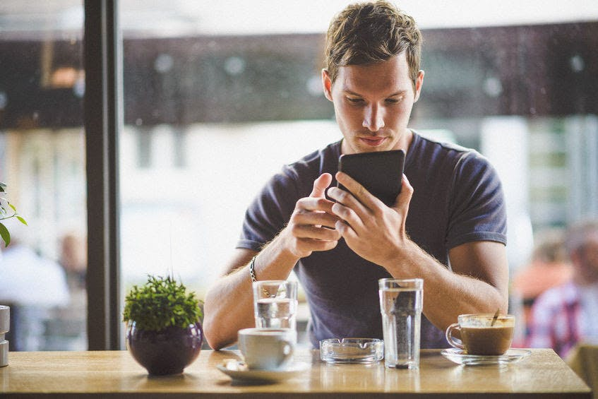 Close-up of young man looking at his smart phone, with 2 cups of coffee and 2 glasses of water in front of him